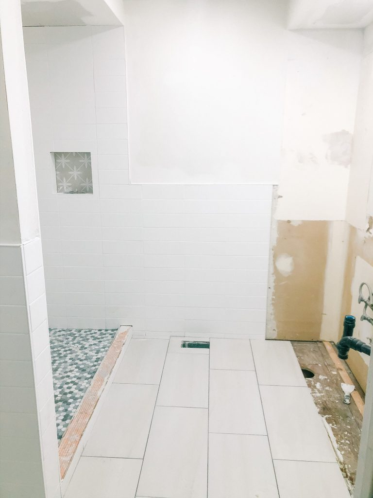 The floor tiles have enough grey to not blend in with the wall tiles, but they do not steal the show from the shower tiles.