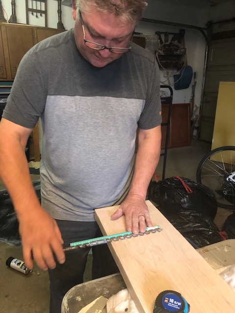 Hubby is illustrating how far the re-bar will go into the mantle and the drill bit he is using.