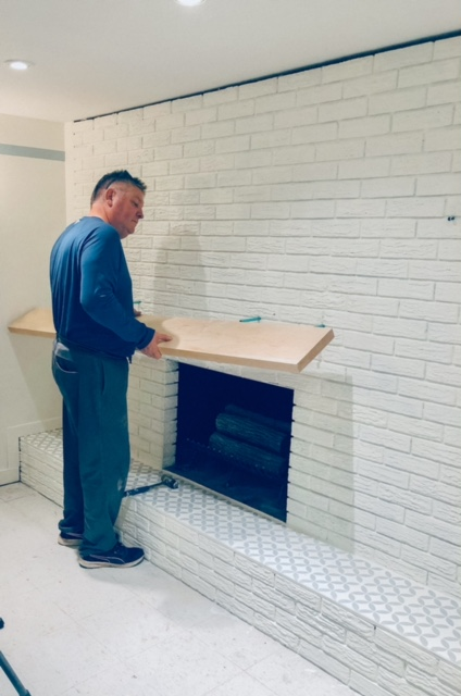 Here is Hubby installing the wood mantle on our fireplace