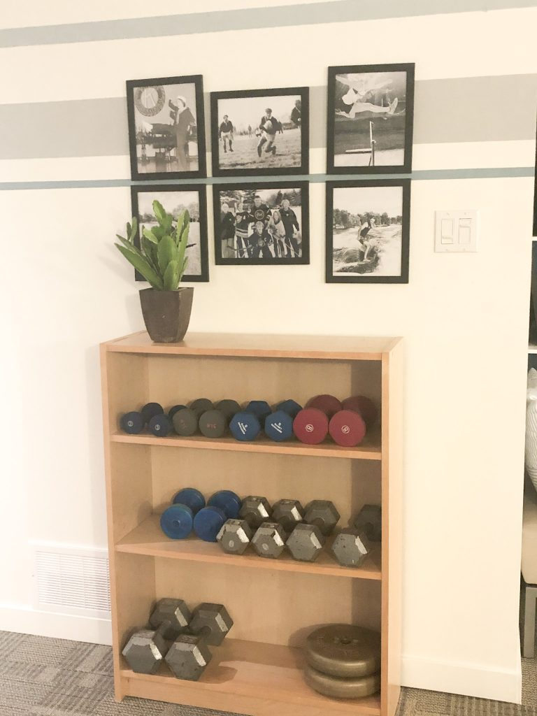 "This book shelf is a great place to store weights.  And we have family motivational pictures above with each of us doing a spot.  The top left is me dancing and singing ""The Sailor with the Navy Blue Eyes.""lol"